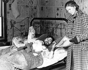 Reading to an invalid wounded by a bullet. Note the newspaper used as wallpaper and insulation.